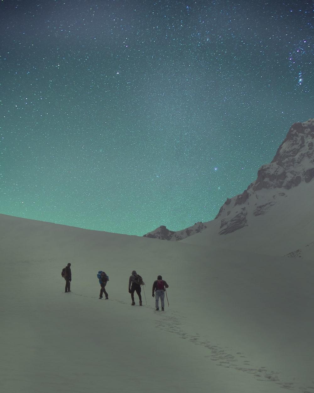 four people walking near mountain