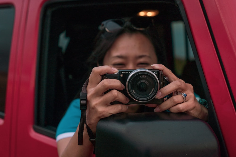 woman holding DSLR camera in red vehicle