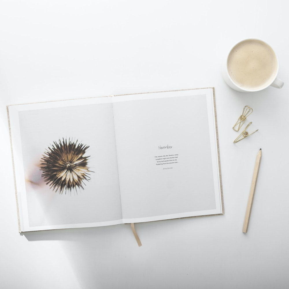 white book beside cup of coffee