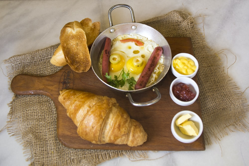 bread beside bowl with eggs and hotdog