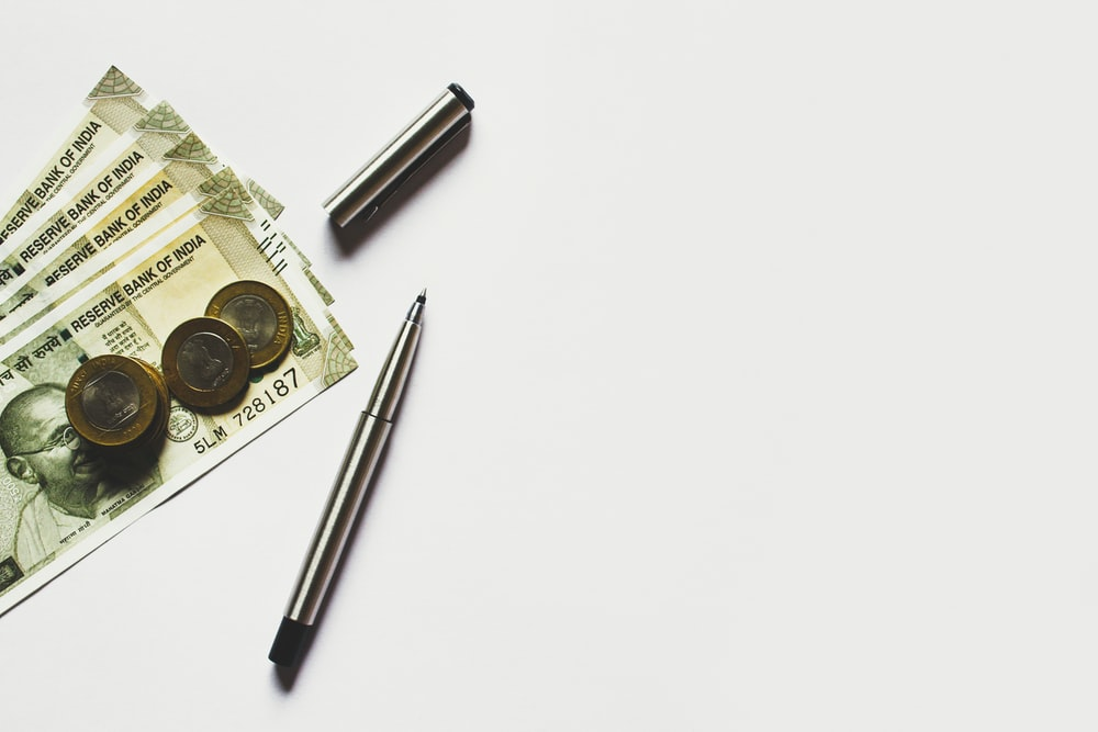 gray pen beside coins on Indian rupee banknotes