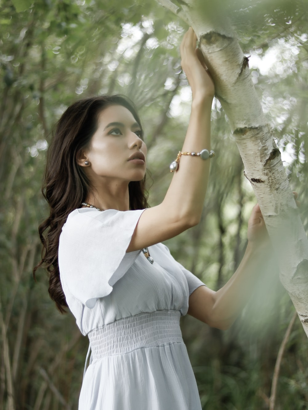 woman holding tree trunk