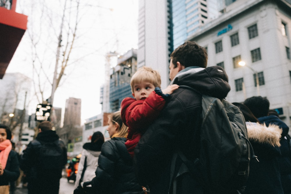 man carrying boy in red jacket