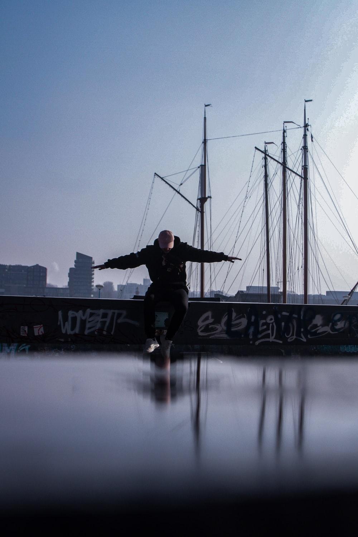 man sitting on concrete on dock