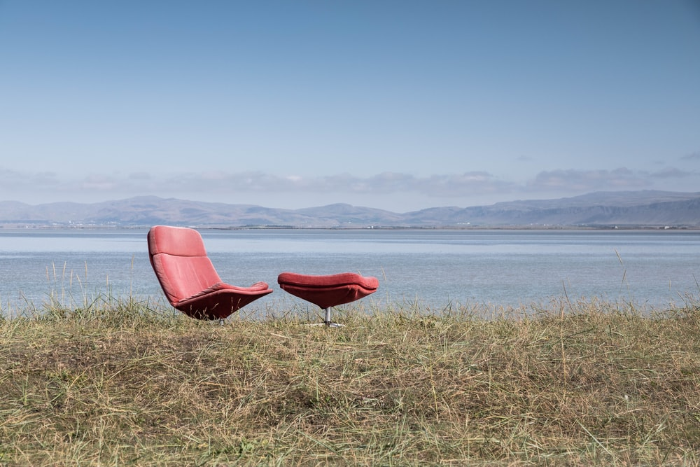 red glider chair beside body of water at daytime