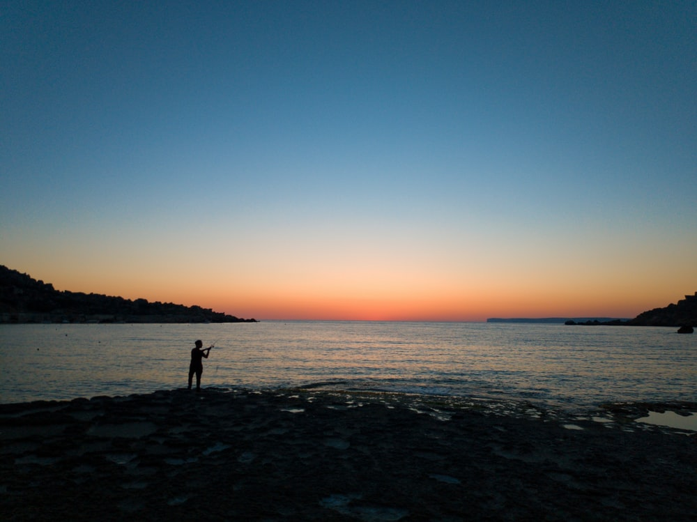 person standing near seashore viewing blue sea under blue and orange skies