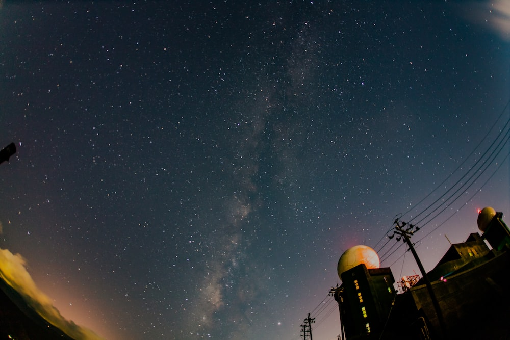 low-angle photo of stars in the sky with silhouette of telephone post