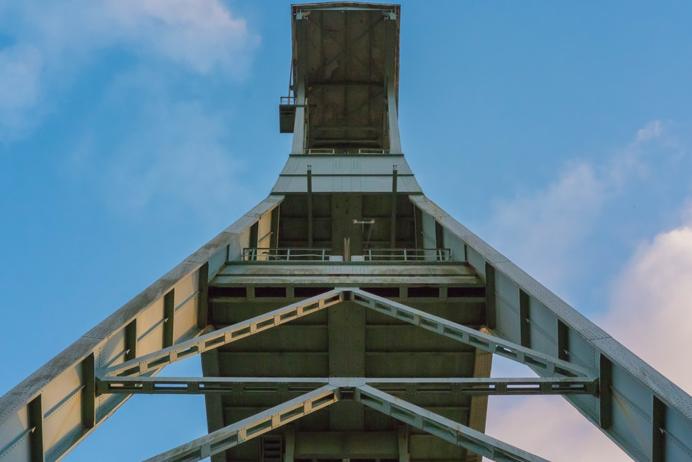 low-angle photography of steel structure under cloudy sky