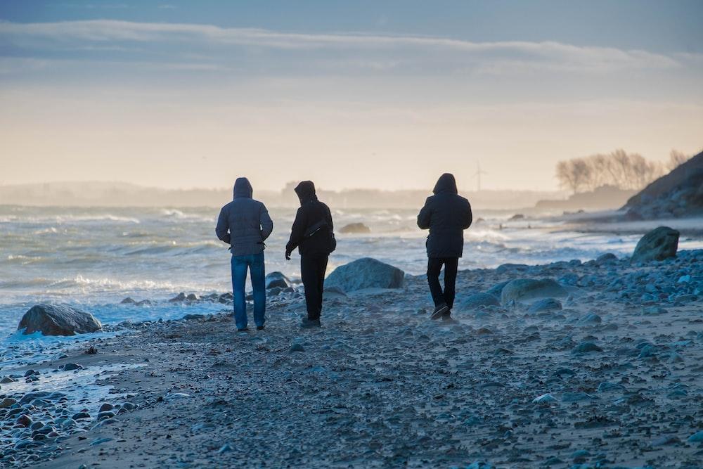 three people in black coats walking on shore