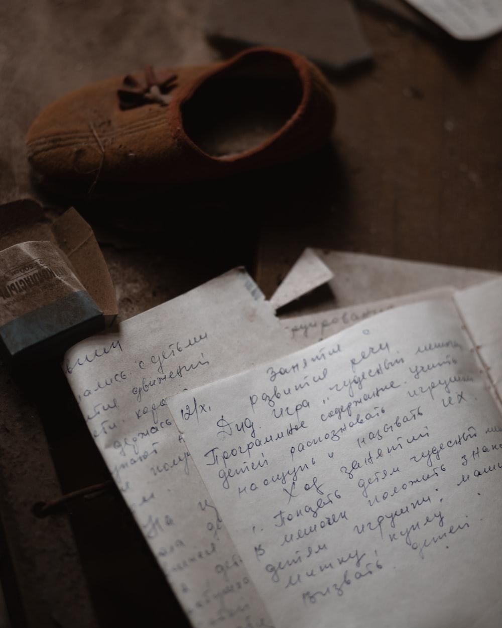 written note book beside brown shoe