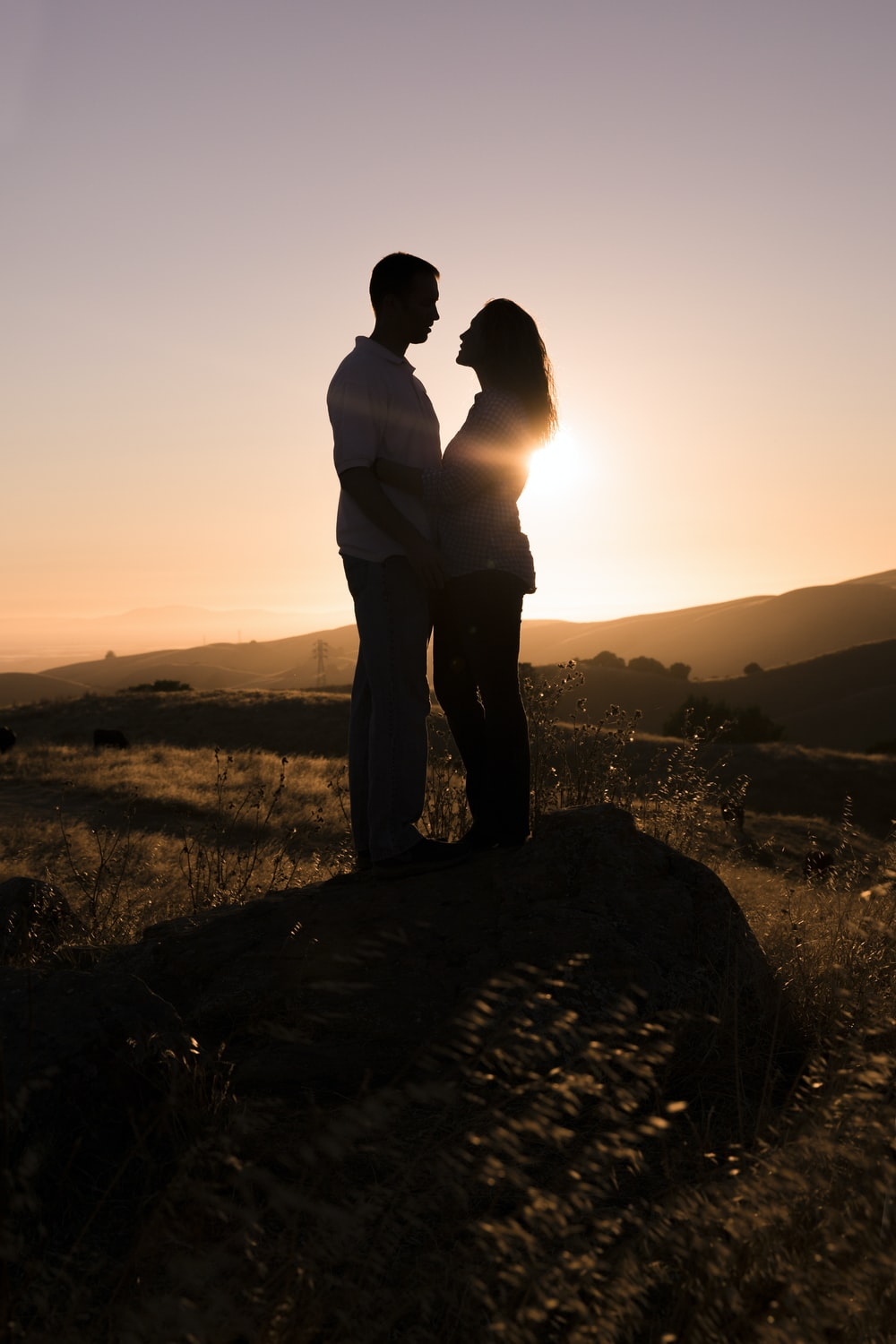 man and woman standing on rock facing each other during day
