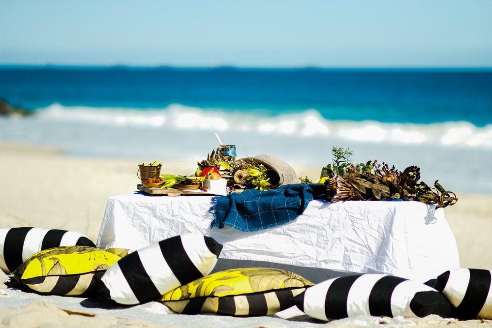 black and white striped pillow near table on beach