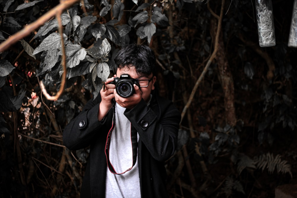 man holding camera beside hedges