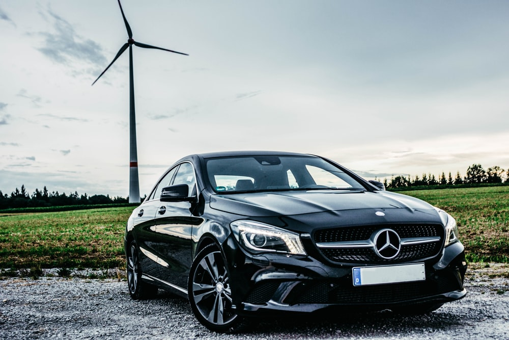 black Mercedes-Benz vehicle park near windmill