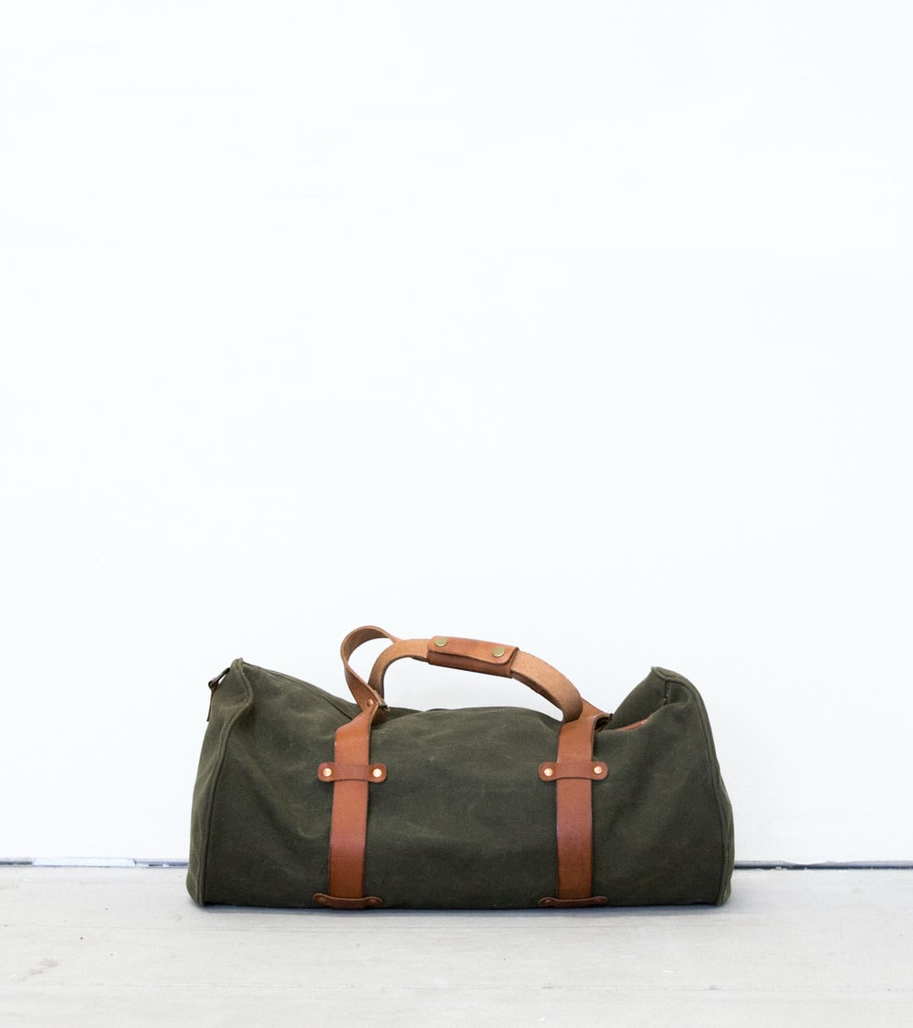 black and brown duffel bag on white surface