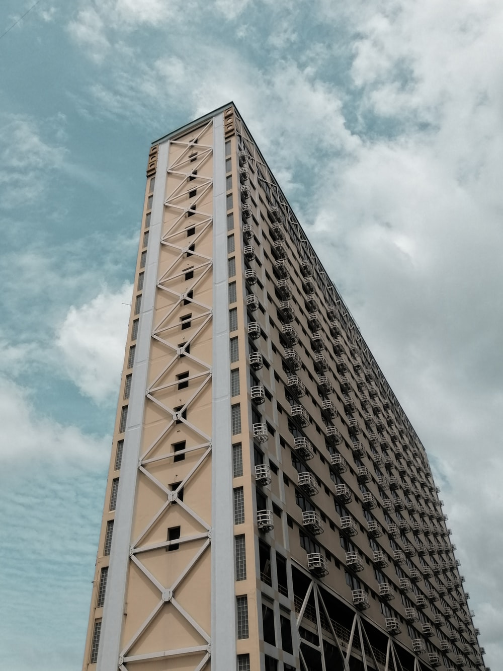 brown high-rise building under blue and white skies