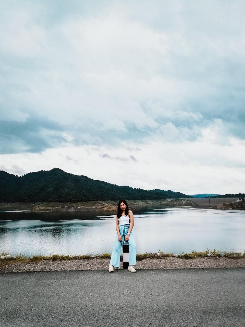 woman in white sleeveless shirt sitting near body of water during daytime