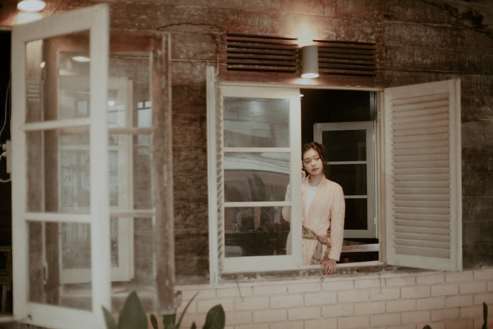 woman leaning on window frame