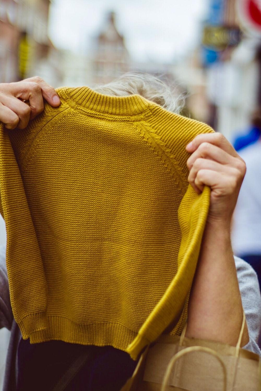 person holding sweatshirt