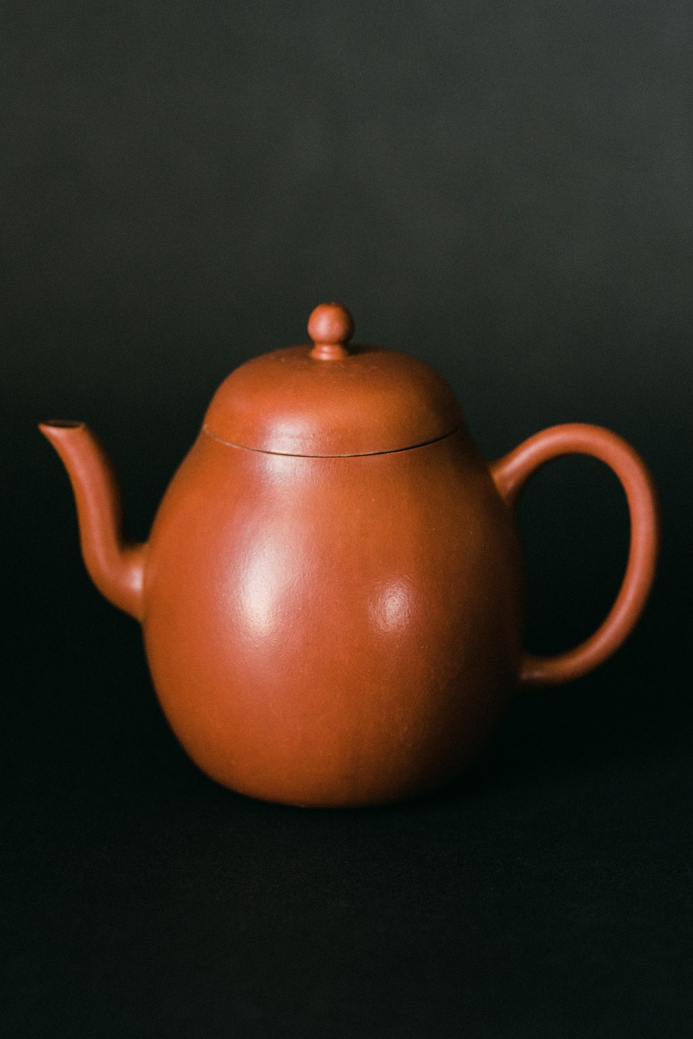 brown teapot on gray surface