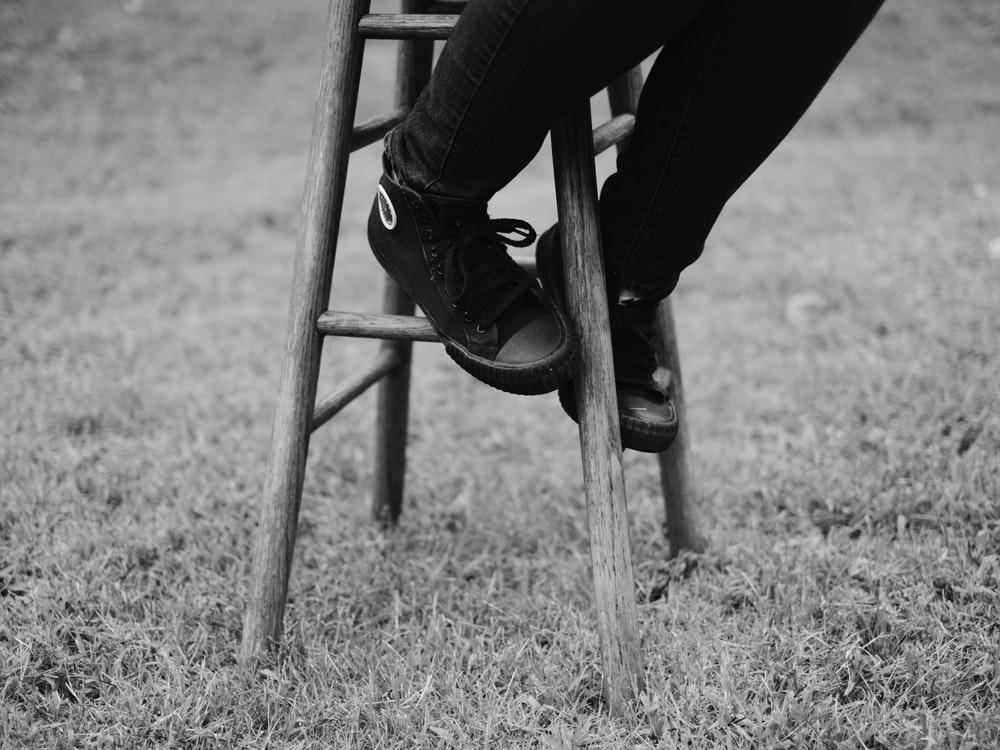 grayscale photo of person sitting on brown stool
