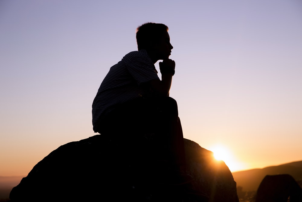 silhouette photography of man sitting on stone