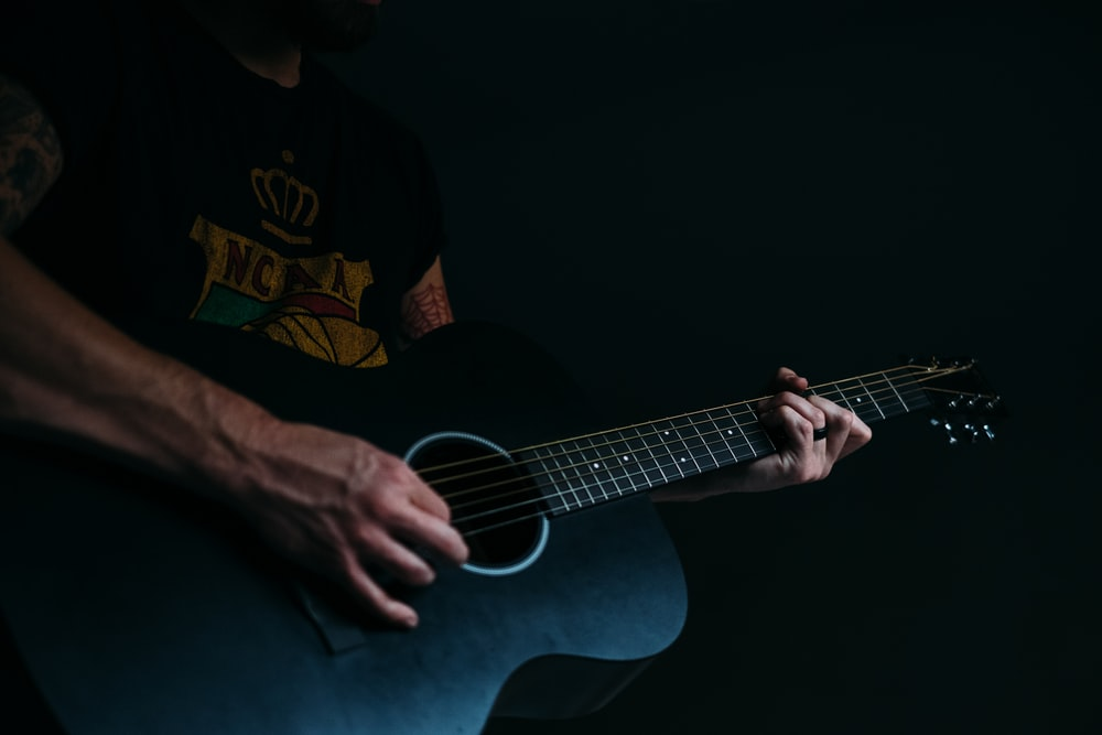 person wearing black and multicolored shirt playing acoustic guitar