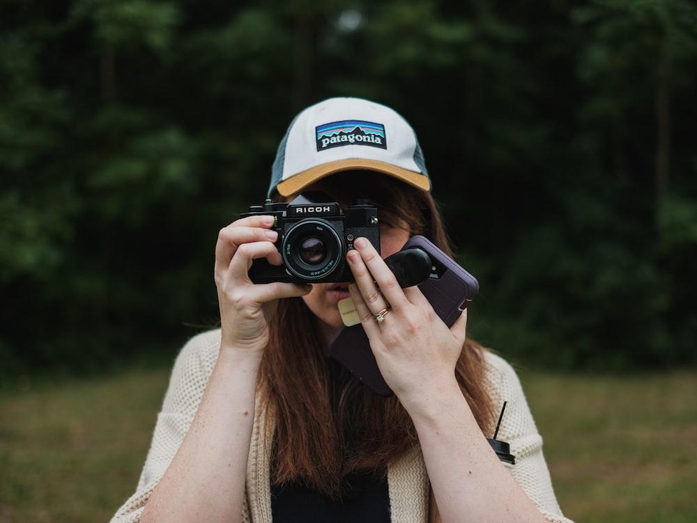 woman about to take a photo using black bridge camera