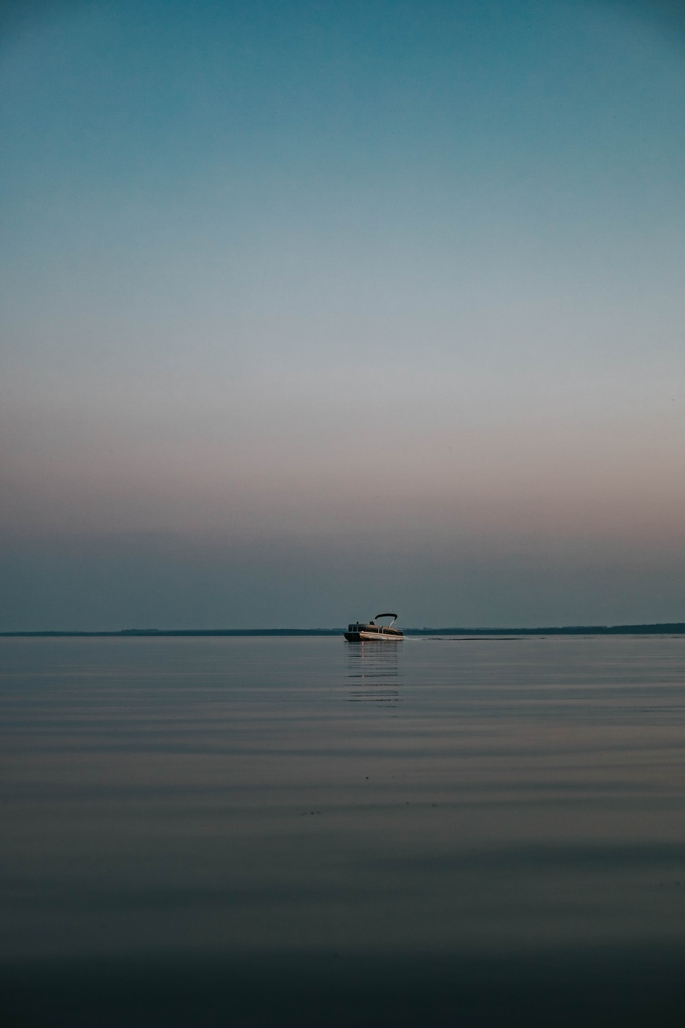landscape photography of speedboat floating in the sea