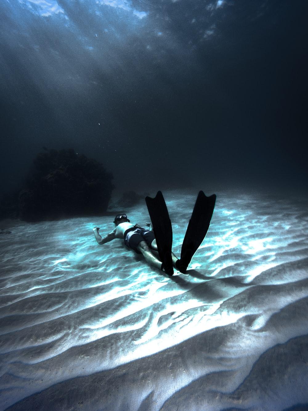 man wearing diving gear lying on sand underwater