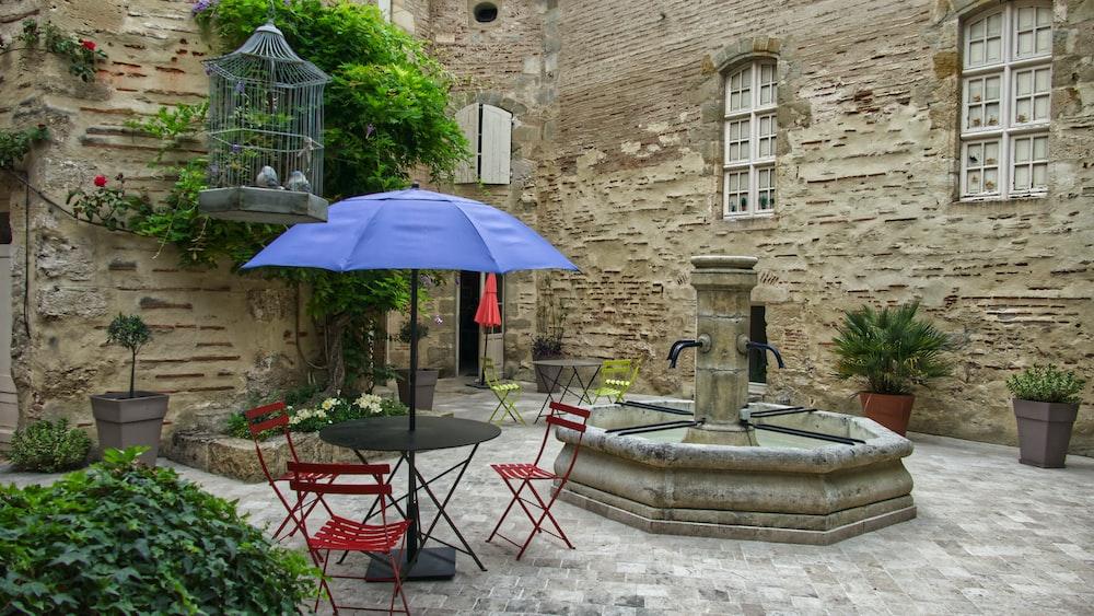blue patio umbrella beside fountain