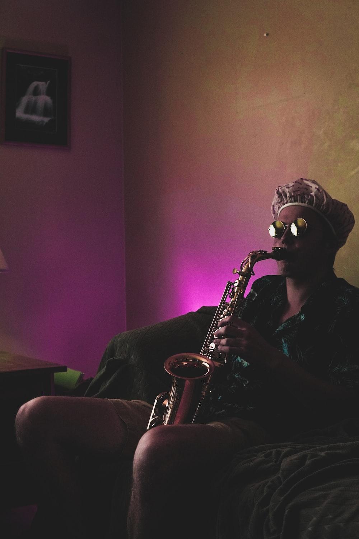 man sitting while playing brass saxophone
