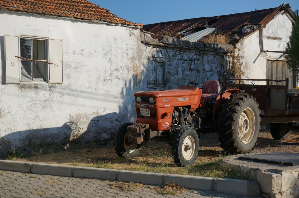 red tractor park beside house