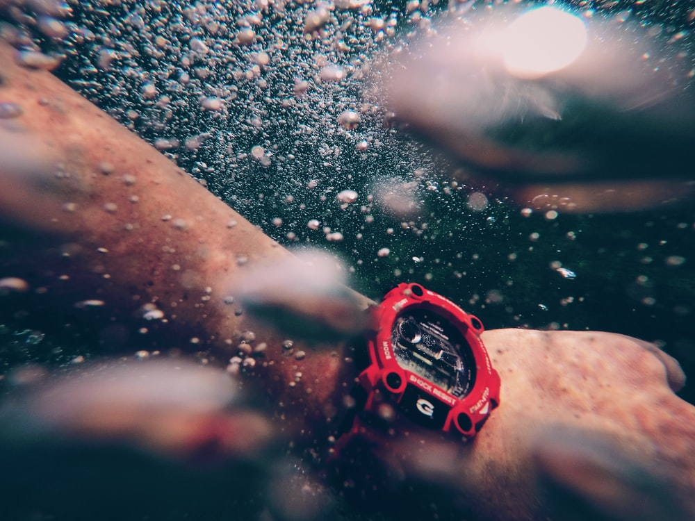 person wearing red and black digital watch