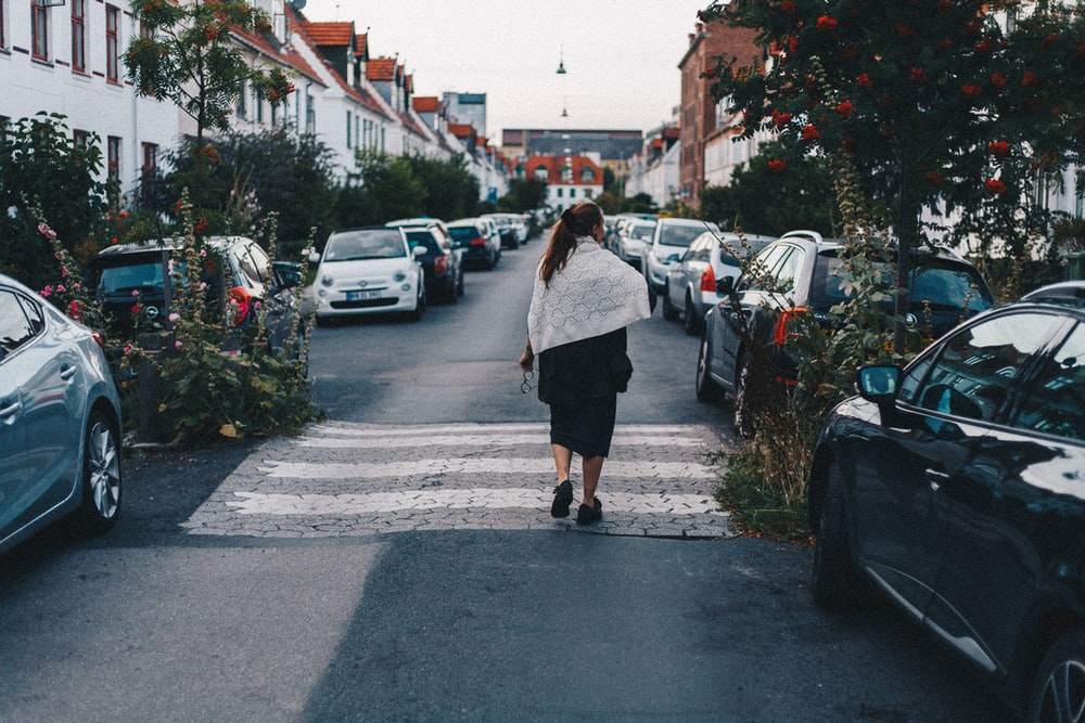 woman walking beside parked vehicles