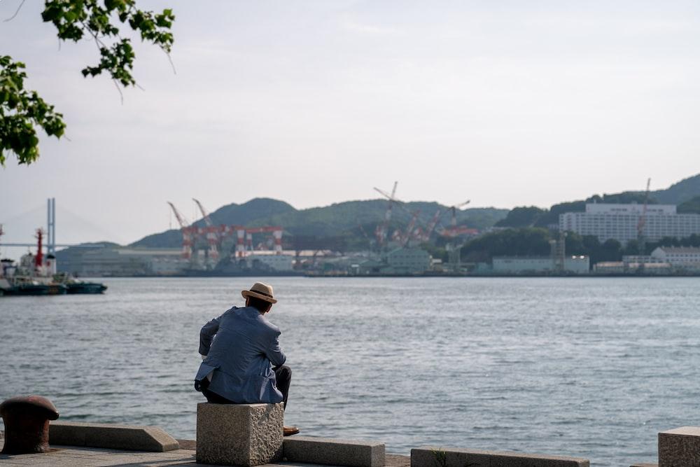 man sitting on rock looking on water