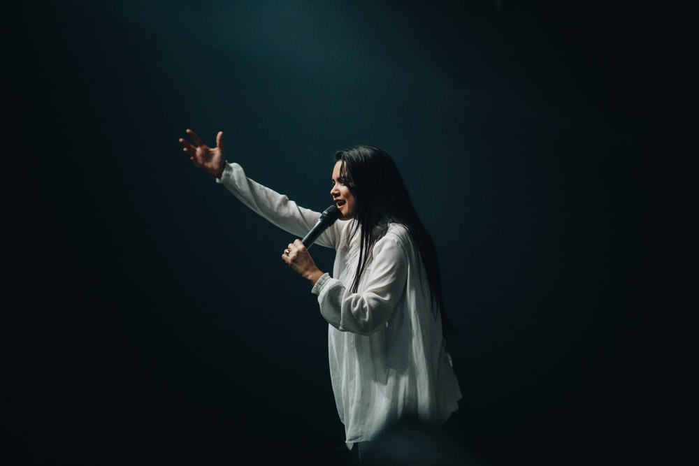 woman in long-sleeved shirt holding microphone