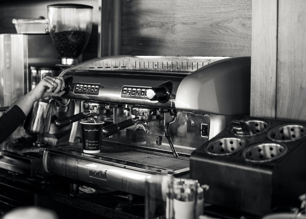 grayscale photography of person using espresso machine