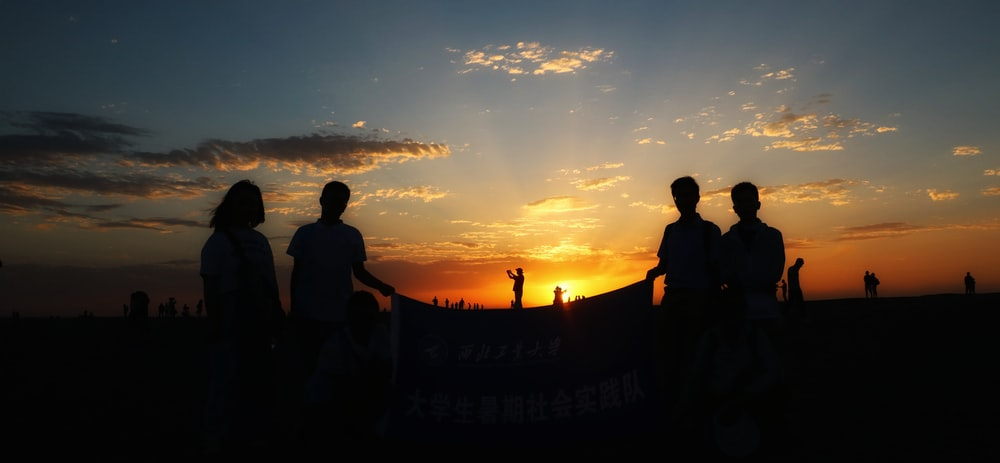 silhouette photography of people under clear blue sky