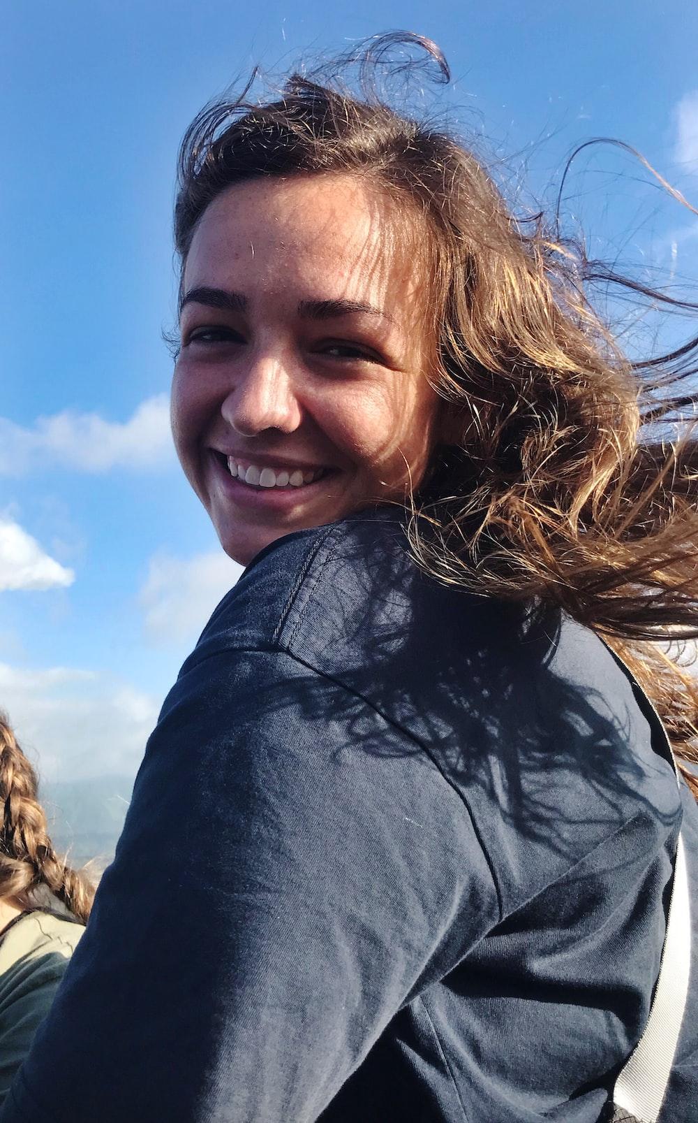 smiling woman wearing blue long-sleeved shirt