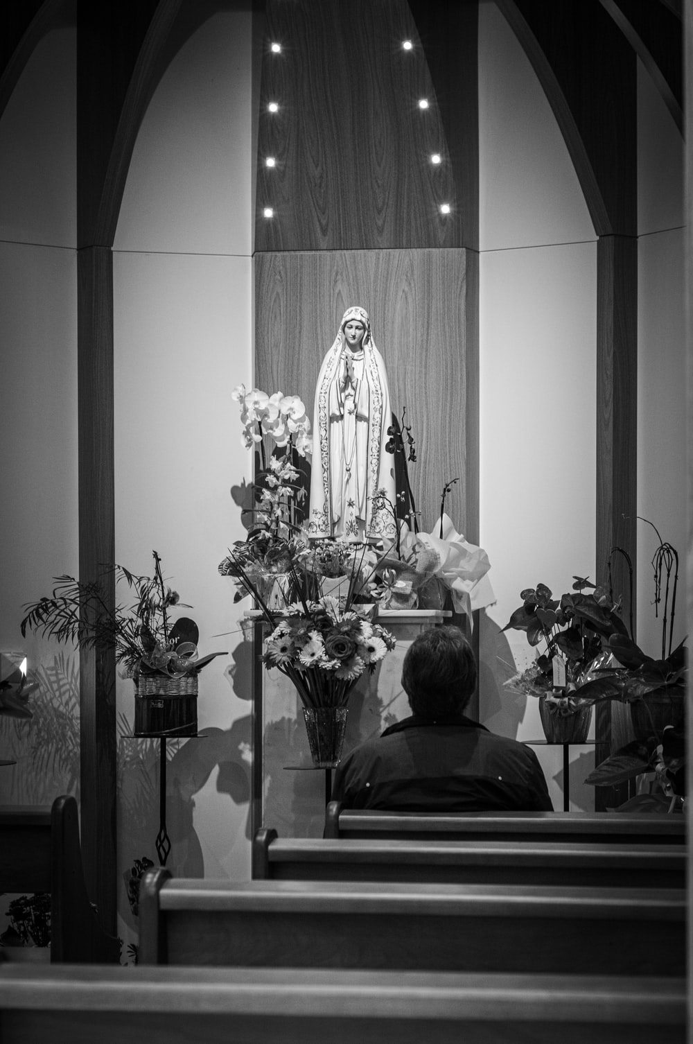grayscale photography of person sitting in front of religious figure