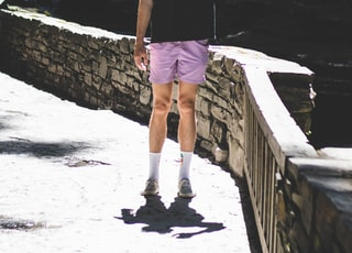man in black crew-neck t-shirt and purple shorts standing beside stone fence