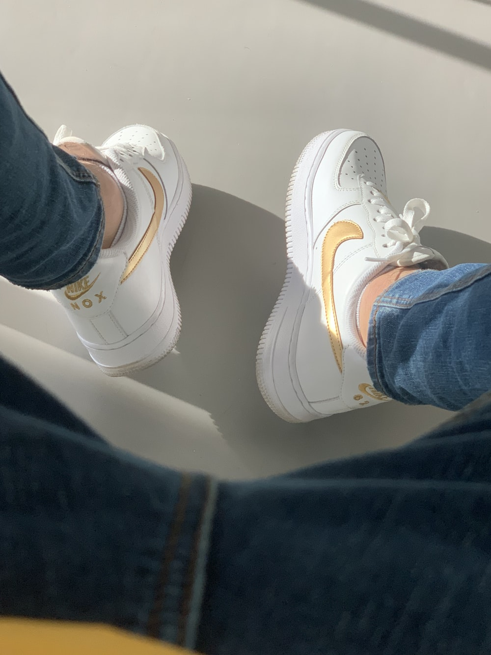 white-and-gold Nike Air Force One sneakers