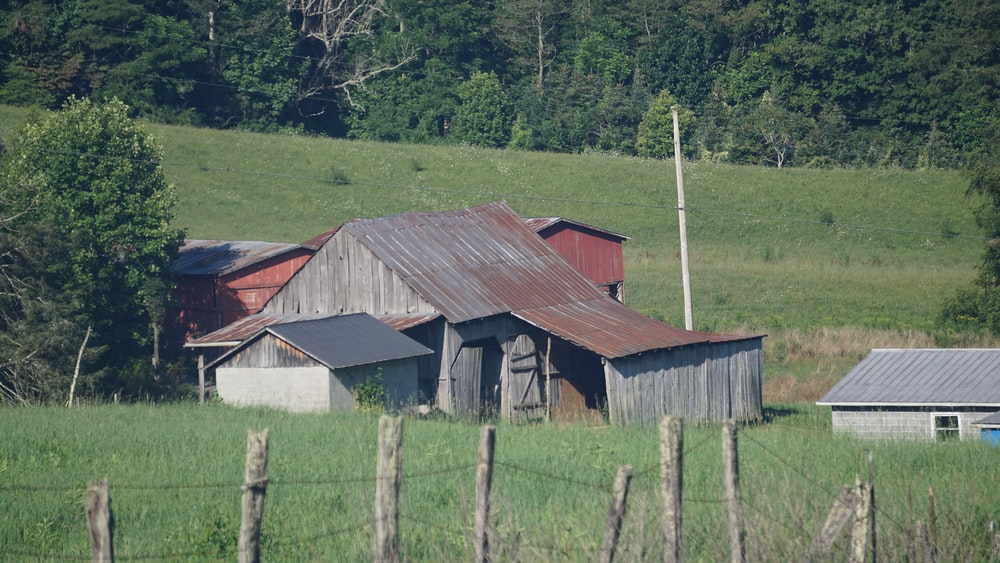 gray wooden barn with gray wooden wire fence
