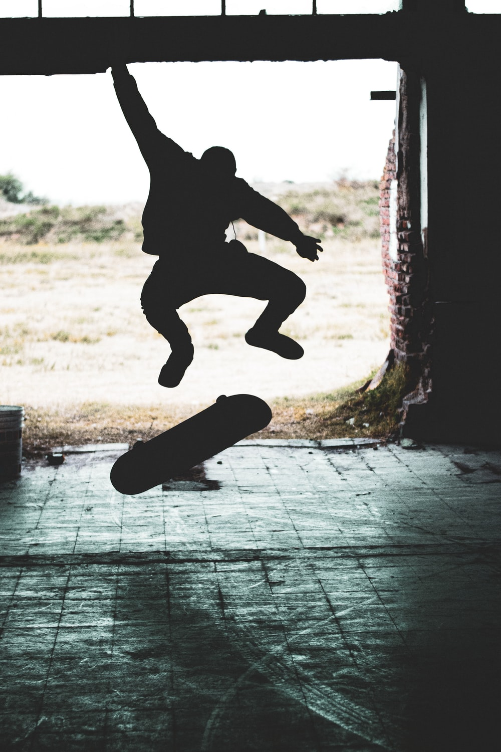 silhouette of person making skateboard stunt during daytime
