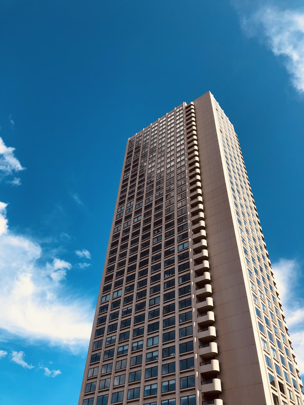 white high-rise building under blue and white skies