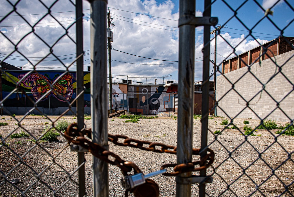 gray stainless steel chainlink fence with lock under blue and white skies