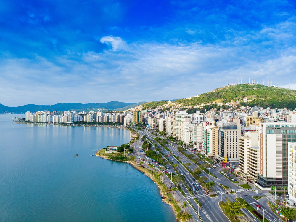 city with high-rise buildings viewing blue sea under blue and white skies