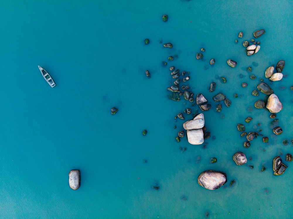 aerial photography of boat floating near rocks