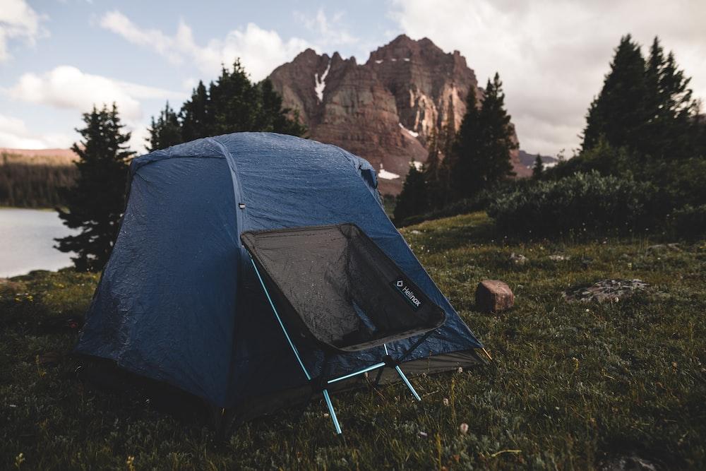 black folding chair beside blue tent near body of wate r